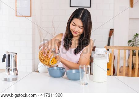 Asian Woman Eating Cereal Breakfast On Kitchen Table In Morning.daily Lifestyle