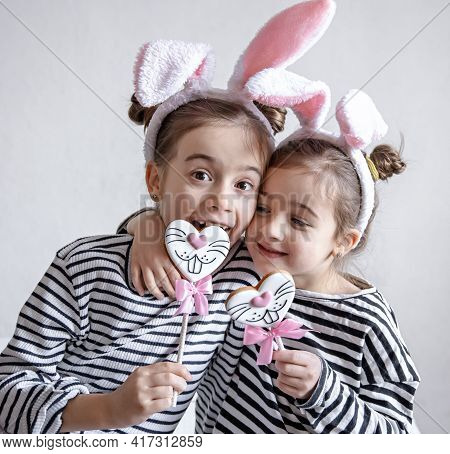 Funny Little Girls With Easter Ears On Their Heads And Easter Gingerbread On Sticks.