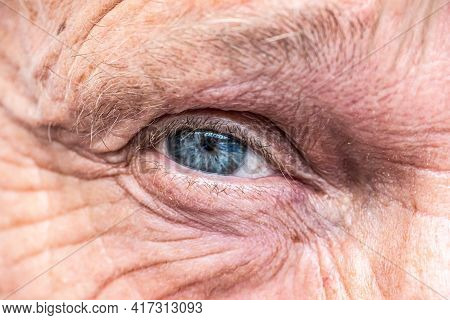 Close-up Macro View On The Blue Eye Of Senior Man Smiling