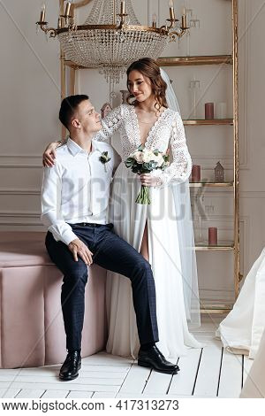 The Groom Gently Hugs The Bride In A Beautiful Lace Dress With A Bouquet Of Fresh Flowers. Wedding P
