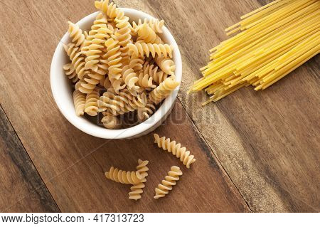 Dried Italian Spiral Fusilli And Spaghetti Pasta On A Wooden Kitchen Table Ready To Be Used As Cooki