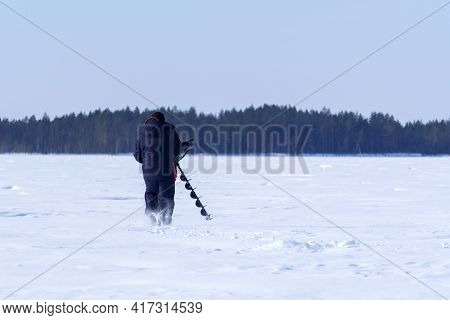 Man Drills Holes In The Ice For Ice Fishing With An Electric Auger. Selective Focus
