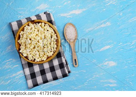 Movie Theater Popcorn In A Bowl On Blue Background, Top View. Classical Popcorn With Sea Salt