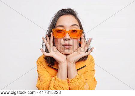 Isolated Shot Of Serious Asian Woman Keeps Hands On Cheeks Wears Tredny Orange Sunglasses And Jacket
