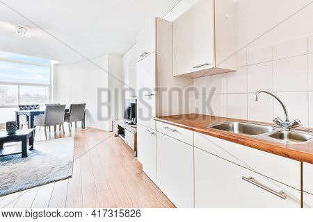 White Cabinets With Wooden Counter Of Modern Kitchen And Dining Table Set In Living Room Of Apartmen