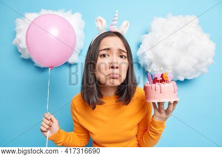 Miserable Asian Woman With Dark Hair Looks Sadly At Camera Celebrates Birthday Alone Holds Delicious