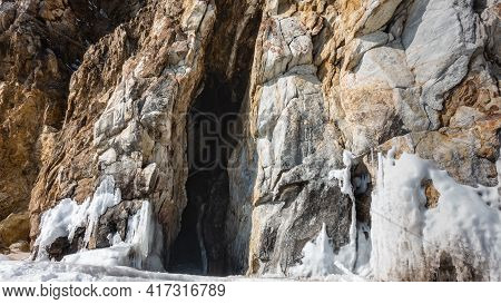 A High Rock Without Vegetation, With Cracks In The Stones. A Narrow Dark Crevice Goes Into The Depth