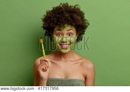 Cheerful Young Afro American Woman Wrapped In Towel Holds Toothbrush Going To Do Morning Daily Routi