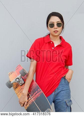 Young Asian Woman In Red T-shirt With Collar Holding The Surfskates Board In Hip Position. While Put