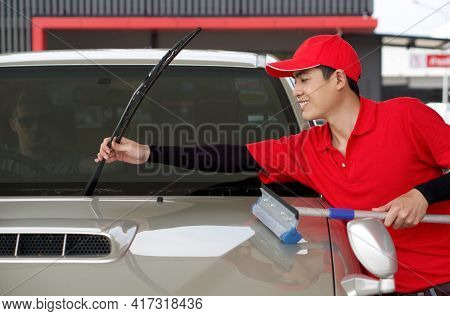 An Asian Gas Station Worker Raises The Windshield Wipers To Clean The Car Windshield. A Caucasian Dr