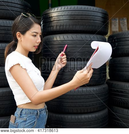 Young Asian Owner Of The Auto Parts Store Checks The Number Of Tires And The Incoming Orders Before