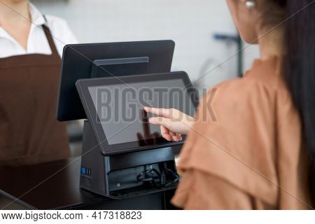 Young Asian Customer Orders A Beverage Menu By Choosing From A Computer Monitor At The Counter. Wait
