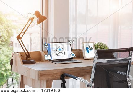 Laptop Screen Was Placed On The Desk By The Window, An Envelope Icon Popped Up. Smartphone And A Pic