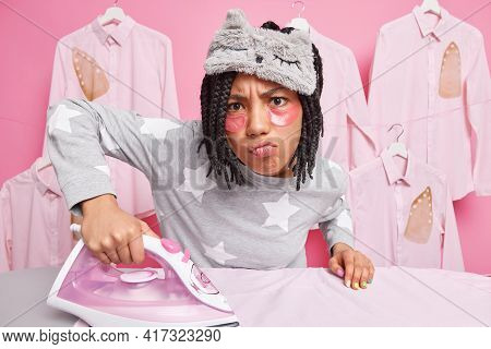 Busy Displeased Housewife Does Ironing Makes Unhappy Grimace At Camera Dressed In Nightwear Irons Hu