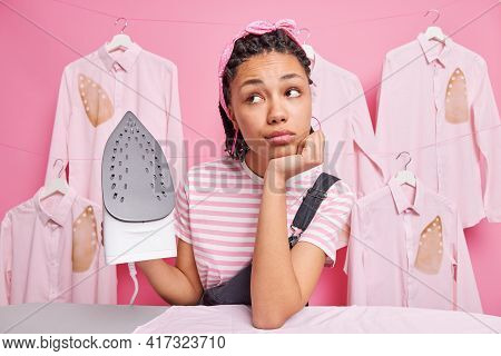 Pensive Millennial Woman Leans On Ironing Board Stands With Daydreaming Expression Uses Appliance Ir