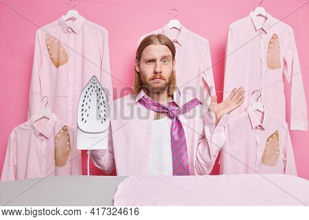 Puzzled Bearded Redhead Man Uses Iron To Get Wrinkles Out Of Shirt Raises Palm While Standing Near I