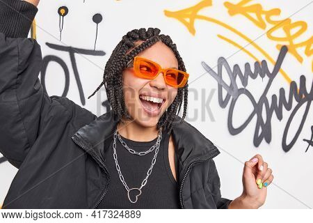 Positive Energetic Dark Skinned Teenage Girl With Dreadlocks Has Fun Dances Against Colorful Graffit