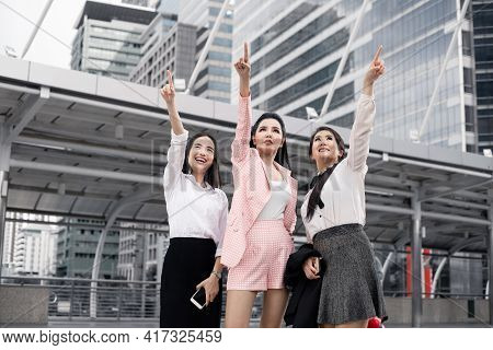 Group Of Asian Business Woman Pointing Forward With A Smile.