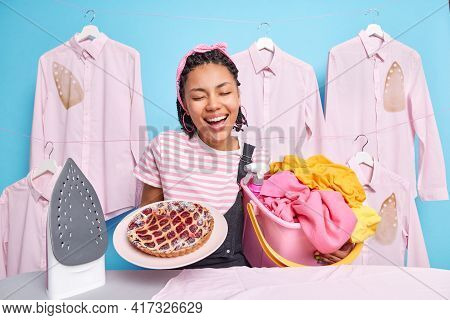 Happy Dark Skinned Woman Glad To Finish All Housework Spends Free Time On Cooking Ironing And Launde