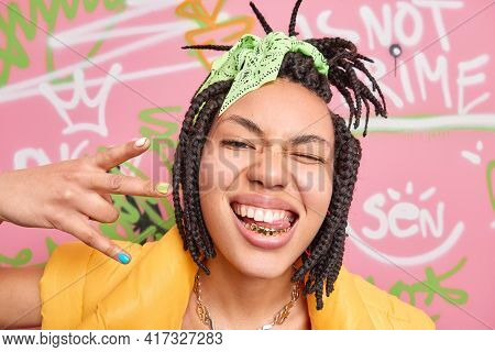Trendy Cheerful Hipster Girl Makes Yo Gesture Shows Golden Teeth And Tongue Winks Eye Enjoys Cool Mo