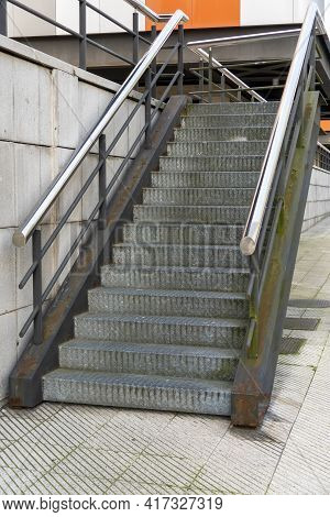 Corrugated Metal Staircase With Shiny Chrome Handrails