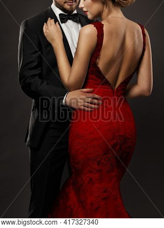 Couple In Love. Romantic Fashion Glamour Woman In Red Dress And Elegant Man In Suit. Black Studio Ba