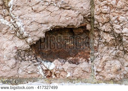 Old Hole From An Artillery Shell On An Ancient Stone Wall