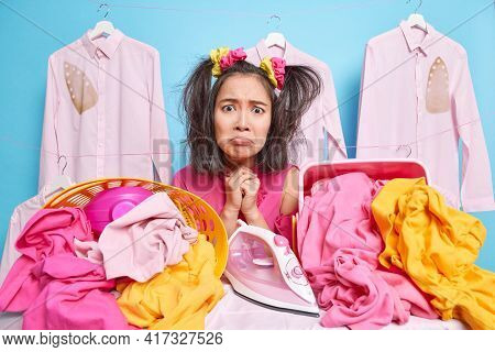 Displeased Young Asian Woman Has Sulking Expression Looks Frustrated At Camera Poses Near Much Laund