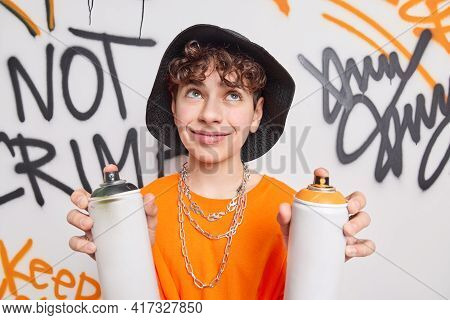 Handsome Thoughtful Curly Haired Teenager Concentrated Above Holds Two Paint Cans Creats Graffiti Wa