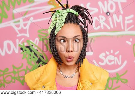 Modern Urban Girl Makes Funny Grimace Crosses Eyes Has Dreadlocks Dark Skin Stands Against Drawn Gra