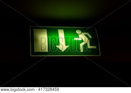 Green Sign Indicating Fire Exit, Arrow Down Straight Exit On Black Background.