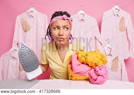 Displeased Dark Skinned Pensive Housemaid Looks Thoughtfully Away Holds Stack On Unfolded Laundry An