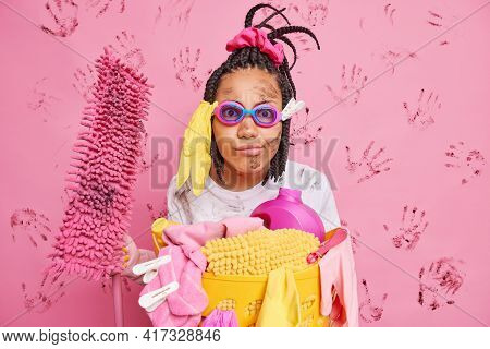 Serious Funny Woman With Dreadlocks Wears Swim Goggles Holds Mop Busy Cleaning House Doing Launderin