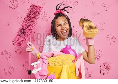 Glad Afro American Woman Wipes Dust In Dirty Room Holds Mop And Sponge Looks Away Happily Does Laund