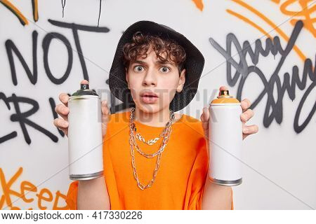 Stunned Handsome Hipster Guy Holds Two Aerosol Spray Bottles Makes Graffiti Wall Wears Hat And Orang