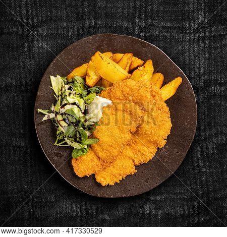 Fried Chicken Breast Fillet With Potato Wedges On Dark Background