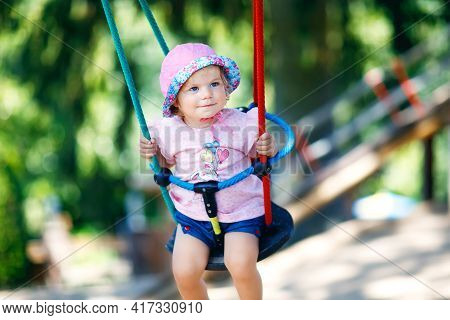 Cute Adorable Toddler Girl Swinging On Outdoor Playground. Happy Smiling Baby Child Sitting In Chain