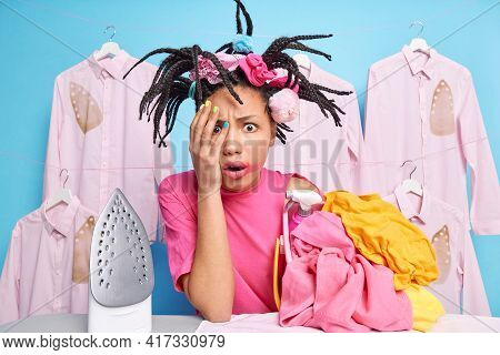 Scared African American Woman Covers Hand With Face Poses Near Stack Of Unfolded Laundry Doesnt Want