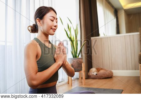 Young Asia Woman Unrolling Roll Black Yoga Mat For Playing Yoga With Her Dog At Home For Quarantine