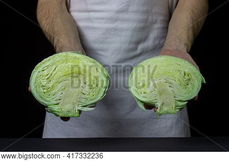 Cabbage On A Dark Background. The Cook Holds Two Halves Of Cabbage On A Black Background. Young Fres