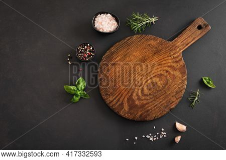 Empty Wooden Round Board With Herbs And Spices On Black Stone Kitchen Table, Top View, Flat Lay. Woo