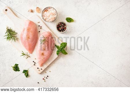 Fresh Raw Chicken Breast Fillet With Herbs And Spices On Wooden Board, Top View, Copy Space. Chicken