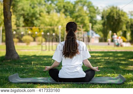 Yoga. A Young Woman In Sports Clothes Meditates In The Park On The Grass. Rear View. Concept Of A He