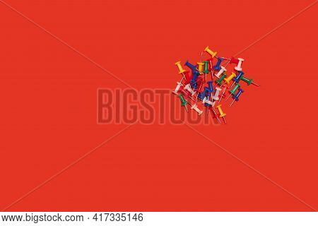 Heap Of Pushpins. Paperclip, Staple, Paperfastener On Red Background