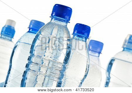 Composition with polycarbonate plastic bottles of mineral water isolated on white background poster