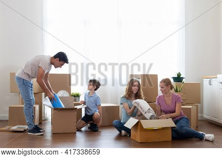 Caucasian Family Pick Up Waste Items And Clothes And Put Them In A Paper Box To Donate And Reuse Or