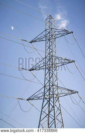 Electricity Pylon With The Moon Against A Blue Sky, Depicting Uk National Grid And Electricity Power