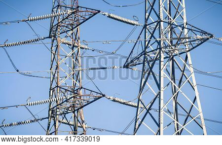 Detail Of Electricity Pylons Against A Blue Sky, Depicting Uk National Grid And Electricity Power Su