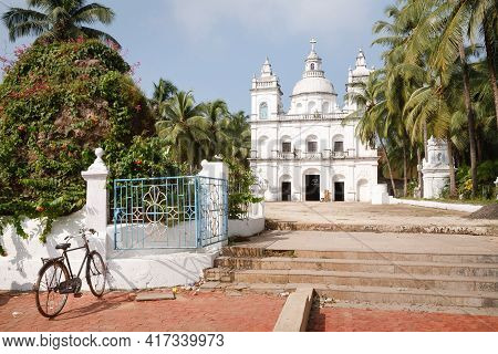 Bicycle Outside The Church Of St Alex, A Large Catholic Christian Church In Calangute, North Goa, In