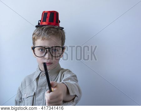 A Cute Little Magician With A Magic Wand In His Hand And A Magician's Hat Shows A Trick On A Light B